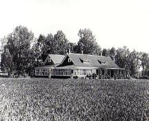 The photo dates from circa 1927 after the completion of the addition to the ranch house. The addition with its glazed porch is at the rear left hand side.; Glenbow Museum NA-460-22