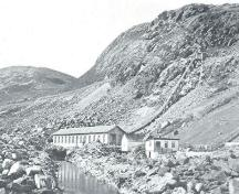 "Petty Harbour Hydro-Electric Generating Station, c1900. Photo shows Newfoundland's first hydro-electric generating station, with the original line of the penstock half-way up the ridge.; From: Moses Harvey ""Newfoundland at the Beginning of the 20th Century: a treatise of history and development."" (New York: South Pub. Co., 1902) 176."