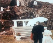 Pope John Paul II kneeling to pray at the front of Our Lady of Lourdes Grotto, Flatrock, 1984/09/12.  ; Courtesy Flatrock Grotto Committee.