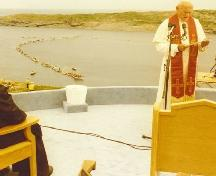 Pope John Paul II at the Blessing of the Fleet and Homily Site, Flatrock, with boats in the harbour in the background, on 1984/09/12.; Courtesy Archives of the Roman Catholic Archdiocese, St. John's, NL.