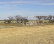 View northeast showing gate, fence, memorial cairn and wooden cross, 2005.; Government of Saskatchewan, Marvin Thomas, 2005.