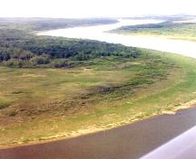 Aerial view looking north at site area on left bank of the South Saskatchewan River, near side of trees, 1999.; Margaret Kennedy, 1999.