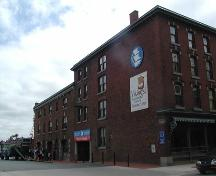 Robertson's Hardware & Warehouse, north side view from Lower Water Street, large warehouse doors, paired windows, bracketed eaves, Halifax, Nova Scotia, 2005.; Heritage Division, NS Dept. of Tourism, Culture and Heritage, 2005.
