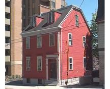 Story-Wilson House, Side elevation showing truncated gable roof and large apartmetn in backgound, Halifax, Nova Scotia, 1997.; HRM Planning and Development Services, Heritage Property Program, 1997.