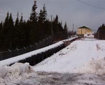 Exterior view of the wooden flume constructed by Bernard J. Miller (1877-1949).  This flume was the first of its kind built in Newfoundland. The substation can be seen in the upper right corner. Photo taken January 2006.; HFNL/ Lara Maynard 2006.