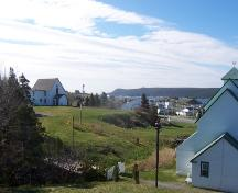 View of the Presentation Convent Grounds, Renews, NL. Covent was located on raised section, adjacent to the rectory on the left. Photo taken May 2006. ; HFNL/Andrea O'Brien 2006