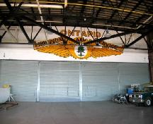 View from outside of original hangar looking at logo painted above roll-up hangar doors; City of Sault Ste. Marie