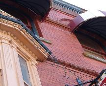 203 Water Street, detail of trims, dentil, egg and dart and sawtooth; also showing hooded canopies over arched windows.  Photo taken July 12, 2006; HFNL/ Deborah O'Rielly 2006.