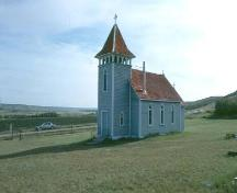 View of Kennell Anglican Church from South-West featuring the typical form and distinctive colours of the church, 1983.; Government of Saskatchewan, Frank Korvemaker, 1983