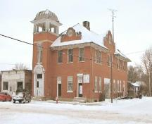View of the front elevation of the Craik Town Hall featuring the brickwork and tower.; Saskatchewan Architectural Heritage Society, Frank Kovermaker, 2005.