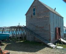 Exterior view of fish flake and of gable end and entrance side of the net store of Samuel Abbott Fishing Room, Newman's Point, Bonavista, NL, circa 2006; Bill Abbott/HFNL 2006
