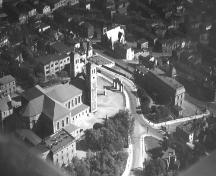 Aerial view of the Basilica of St. John the Baptist and the Basilica Archway.  Other ecclesiastical buildings can also be noted in the picture.  Archway is located near the center right.  Date of photo unknown.; City of St. John's Archives 2006