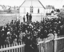 Historic image of crowd with Society of United Fishermen Lodge #9 in the background, circa 1942.  Photo taken from Christ Church property, Church Street, Bonavista, NL.; HFNL/ 2006