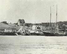 Historic photo of Reddy Premises, circa 1902.  Photo shows the Reddy Premises, including the fisheries buildings, schooners and the Reddy House prominently situated on a high hill above the water. ; HFNL 2006.