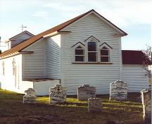 Gable end view of St. Luke's Anglican Church with headstones in foreground, some dating to the 17th century.; HFNL/ 2006