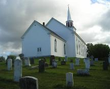 Rear and west elevation and cemetery, St. Peter's Church, Tracadie, Nova Scotia, 2005. ; Heritage Division, NS Dept. of Tourism, Culture and Heritage, 2005.