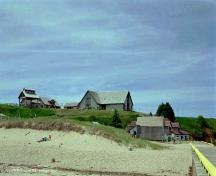 Showing beach in foreground, and museum building on hill above Cannery; Province of PEI, 1999