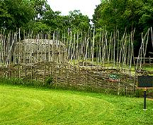 Lawson site reconstructed  palisade and longhouse.; London Museum of Archaeology, 2003