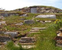 Front photo view of Jim Goodland Upstairs Root Cellar, showing rock stairs ascending from base of hill to cellar, Maberly, Elliston, NL, 2006/06/15; L Maynard, HFNL, 2007