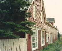 Showing wood shingled exterior and bracketed cornice above ground floor windows; Province of PEI
