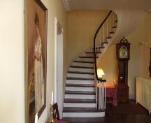 This photograph shows the spiral staircase and the portrait of Mrs. Ross in the foreground to the left, 2007.; Town of St. Andrews
