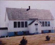 Showing front facade with sign above porch and high pitched roof; Province of PEI