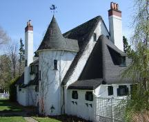 This photograph shows the contextual view of the building and illustrates the turret, tall stucco and brick chimneys, and immitation thatched roof, 2007; Town of St. Andrews