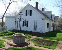 This photograph shows the well with wrought iron cupola at the centre a formal garden. The east side of Cory Cottage is in the background, 2007; Town of St. Andrews