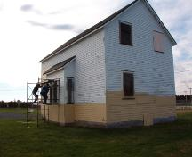 Exterior view of the Bay Roberts Railway Station showing men working on the facade.  They are painting to help protect the exterior until restoration can occur. Photo taken October 17, 2007.; HFNL/ Deborah O'Rielly 2007