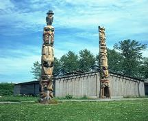 View of the Gitwangak Battle Hill National Historic Site of Canada, showing Gitwangak totem poles in front of a building.; Parks Canada Agency / Agence Parcs Canada