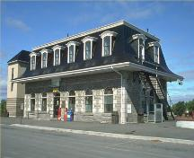 Corner view, showing the facade and a side of the Belleville railway station, 1990.; Parks Canada Agency/ Agence Parcs Canada, 1990.