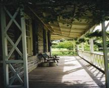 View of the verandah on the north side of house showing bell-cast slope of the roof - 2003; OHT - 2003