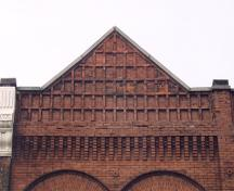 View of the pediment on the east elevation showing corbelling and emboss patterning – April 2003; OHT, 2003