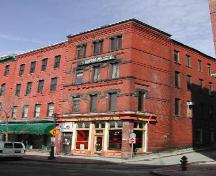 This image shows a full contextual view of the building showing the recessed brick courses on Grannan Street and the relationship the building has with the neighboring building on Prince William Street; City of Saint John 2004