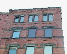 Photograph showing the upper stories and illustrating the windows, recessed brickwork, sandstone ledge, cornice, corbel bands, and sandstone courses; City of Saint John 2004