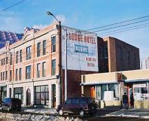 This image illustrates the front, south-facing, primary brick-clad facade of the building showing the storefronts at ground level with two floors of residential uses above. Also illustrated is a large painted sign on the east facade.; City of Edmonton, 2004