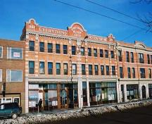 This  image illustrates the front, south-facing primary facade of the building looking from the southwest. The adjacent, historic Lodge Hotel is visible on the right.; City of Edmonton, 2004