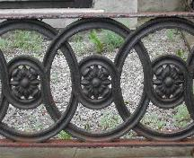 This image shows the circular floral design of the stone and cast iron fence around the front lawn that reflects the pattern specifically created for the Girl Guide cookies, 2005.; City of Saint John