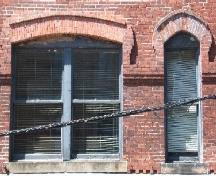 This photograph shows a double window and some of the brick design, 2005.; City of Saint John