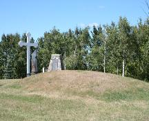 Contextual view, from the southeast, of the Ukrainian Pioneer Mass Grave Site, Oakburn area, 2006. The grave mound is identifiable as the mound in the foreground.; Historic Resources Branch, Manitoba Culture, Heritage and Tourism, 2006