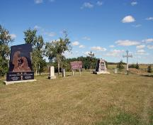 Contextual view, from the southwest, of the Ukrainian Pioneer Mass Grave Site, Oakburn area, 2006, showing the range of commemorative markers at the site.; Historic Resources Branch, Manitoba Culture, Heritage and Tourism, 2006