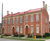 East facing façade featuring round-headed entrance portals, and brick cornice, 2003.; Department of Planning, City of Brantford, 2003.