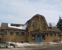 The facade of the Beatty Pool, featuring a unique arched entrance door and gambrel roof.; Lindsay Benjamin, 2007.