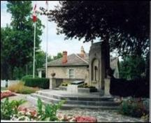 The John McCrae Monument and Memorial Gardens, with the John McCrae home in behind.; Beth McCracken, date unknown.