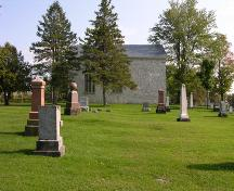 Side view showing stone filled window and cemetery-2006; OHT, 2006