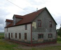Corner view of the building illustrates the medium-pitched gable roof, slight roof overhangs of simple design, and gabled dormers typical of period small-scale industrial and farm buildings. ; PNB 2004