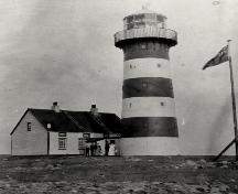 View of Cape Pine Lighthouse, showing the form and massing of the 15.3 metre high structure which consists of a tall, tapered tower with twelve-sided lantern.; Agence Parcs Canada / Parks Canada Agency.