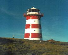 View of the Cape Pine Lighthouse, showing the smooth, painted finish of the exterior walls with its distinguishing colour scheme of alternating white and red, 1990.; Agence Parcs Canada / Parks Canada Agency, 1990.