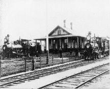 View of first railway station with two steam locomotives, circa 1880; McAdam Historical Restoration Committee