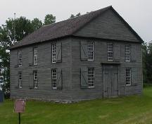 General view of Old Hay Bay Church, showing the two-storey, box-like, rectangular massing set under a medium-pitch gable roof, 2002.; Parks Canada Agency / Agence Parcs Canada, 2002.